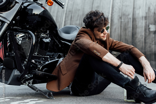 Fotografiet man in stylish brown jacket sitting on ground near motorcycle, looking away and