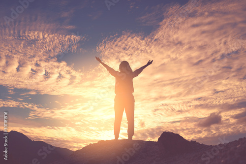 Montage in der Fensternische Cappuccino Copy space of woman rise hand up on top of mountain and sunset sky abstract background.