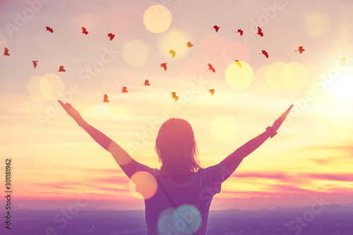 Freedom feel good and travel adventure concept. Copy space of silhouette woman rising hands on sunset sky at top of mountain and bird fly abstract background.