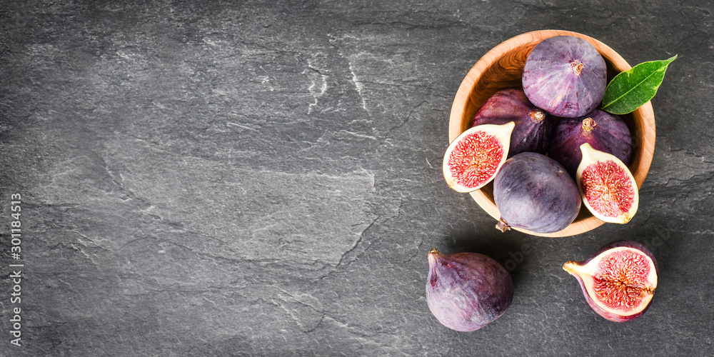Fototapety, obrazy: Fresh figs in round wooden bowl on dark stone table, space for text. Ripe fig fruits with leaves on black texture board. Banner or panorama concept top view.