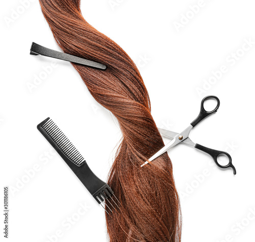 Hair strand and hairdresser's tools on white background