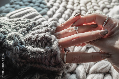 Obraz  Close up of an elegant engagement diamond ring on woman finger with dark gray sweater winter clothe. love and wedding concept.soft and selective focus. - fototapety do salonu