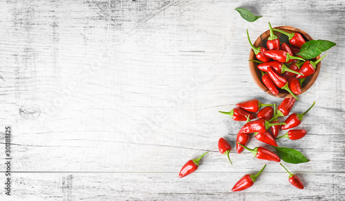 Foto op Aluminium Hot chili peppers Red hot chili peppers on white table copy space. Spicy pepper in bowl top view.