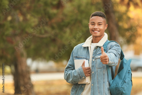 Portrait of teenage African-American student showing thumb-up outdoors