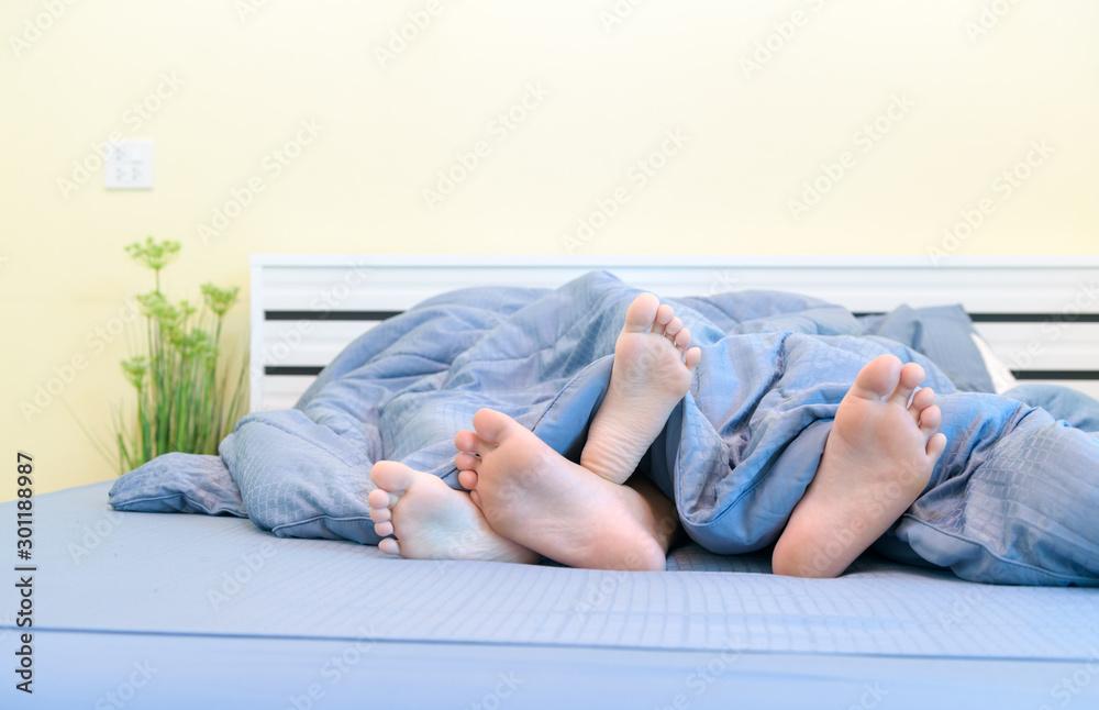 Fototapeta Two pairs of feet of kids under blanket in bed,
