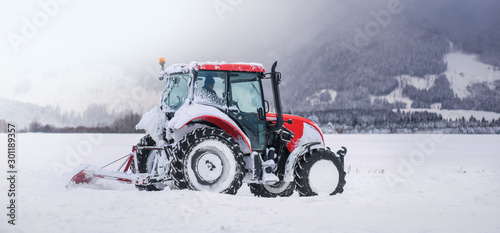 Tractor in winter plowing street or road, agricultural and snow on fields.