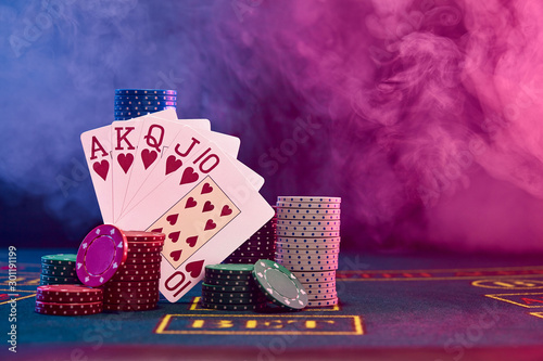 Fotografía Winning combination in poker leaning on colored chips piles on blue cover of playing table