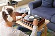 Leinwandbild Motiv Young man listening to music through record player at home