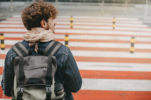 Fotografia, Obraz Young attractive man with curly hair stand in front of crosswalk and look to right