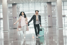 Young Happy Couple Running Through White Empty Airtport. Late On Flight. Worried About Not Being On Time. Vacation Ususal Trip. Unhappy And Scared. Holding Hands Together. Suitcase Behind.