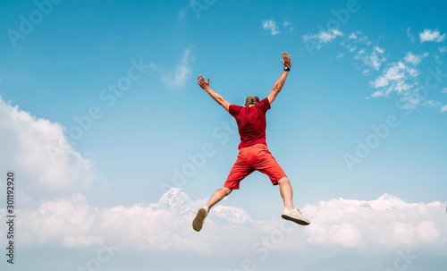 Tableau sur Toile Happy man dressed red jumping over the clouds with Annapurna range mountains on background as he had trekking to Shanti (Peace) Stupa in Pokhara, Nepal