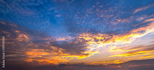 Obraz Panorama Sunlight with dramatic sky. Cumulus sunset clouds with sun setting down on dark background.Vivid orange cloud sky. - fototapety do salonu
