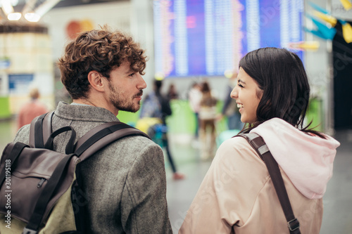 Fototapeta  Young male and female travelers look at each other