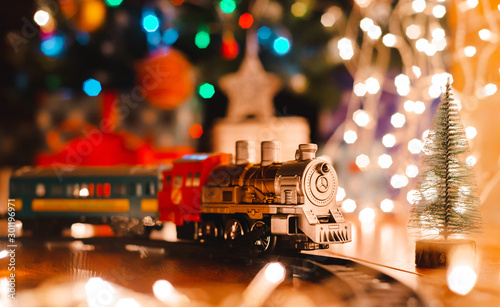 Fotografía  toy vintage steam locomotive on the floor under a decorated Christmas tree on a background of bokeh lights garland