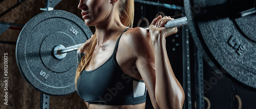Sporty girl is preparing to do barbell squats in a gym. Canvas Print