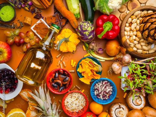 Photo  Mixed colorful foods as nuts, fruits, vegetables, beans, herbs, powders, contains antioxidants, vitamins, fiber