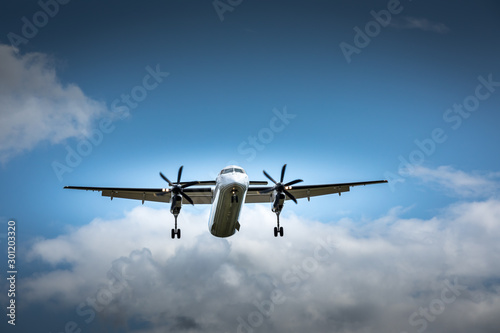 Propeller airplane flying in the cloudy skies Fototapete