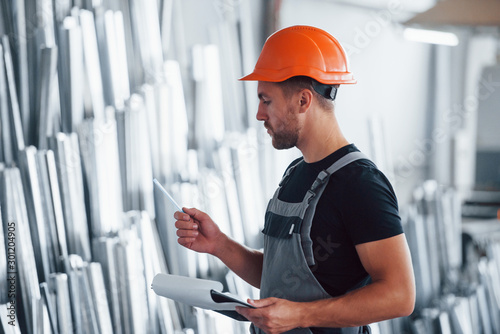 Fototapeta Counting and checking objects in the storage. Industrial worker indoors in factory. Young technician with orange hard hat obraz