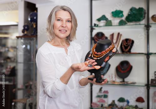 Female seller demonstrates cornelian agate necklace Tapéta, Fotótapéta