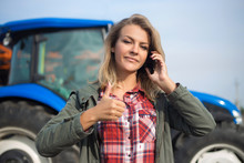 Young Woman Talking On The Phone, Background Of The Tractor With A Thumb Up. The Concept Of Success, Agriculture.