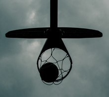 Looking Up At A Basketball Hoop During A Storm