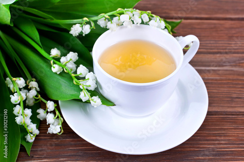 Poster Muguet de mai Cup of green tea with lily of the valley or may bells flowers on a wooden background.