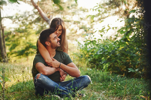 Obraz Sitting and embracing. Beautiful young couple have a good time in the forest at daytime - fototapety do salonu