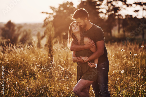 Fototapeta In the field illuminated by the sunlight. Beautiful young couple have a good time in the forest at daytime obraz