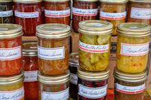 Macro Of Jars Of Homemade Pickles, Jams And Preserves Are Neatly Displayed And Await Buyers At A Farmer's Market.