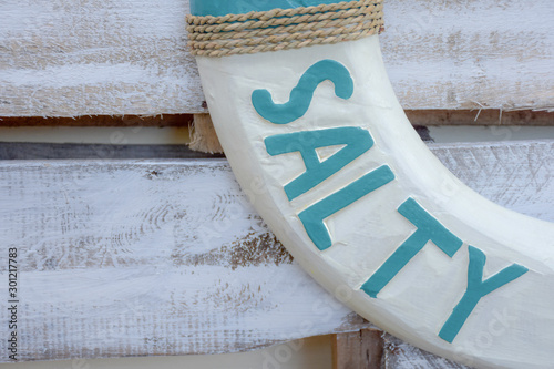 This found typography is carved onto a white and teal wooden life ring or life saver which contains the word SALTY Fotobehang