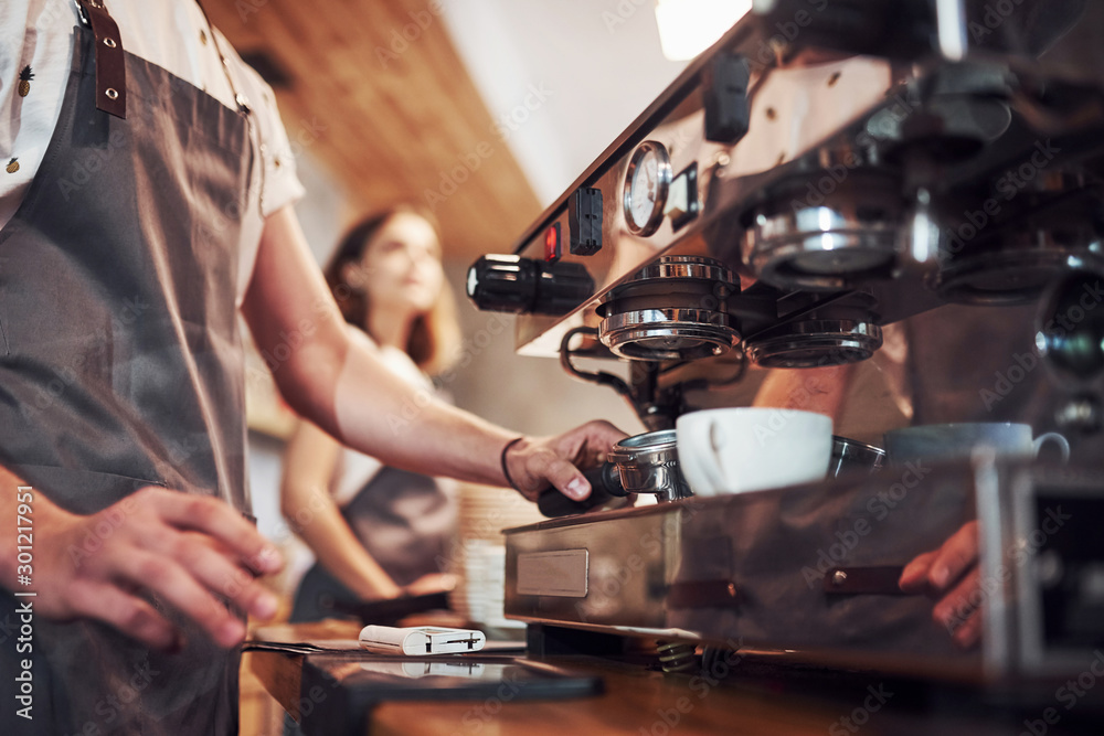 Fototapeta Process of making fresh drink. With machine. Two young cafe workers indoors. Conception of business and service