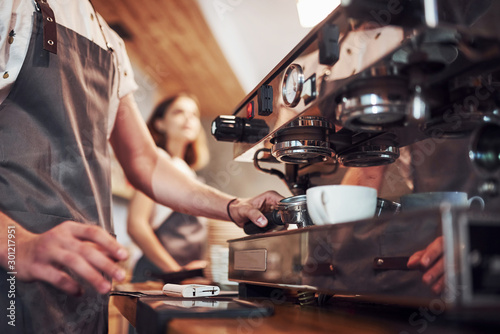Process of making fresh drink. With machine. Two young cafe workers indoors. Conception of business and service