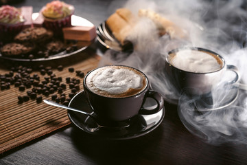 Two cups of cappuccino in hookah lounge. Clay shisha hookah bowl with coffee beans, coffee spices and sweets and chocolate cookies. Clouds of smoke at background.
