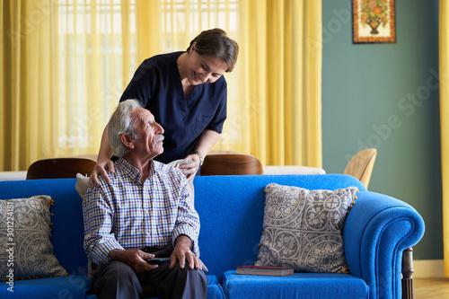 Cuadros en Lienzo  Professional helpful caregiver and a senior man during home visit
