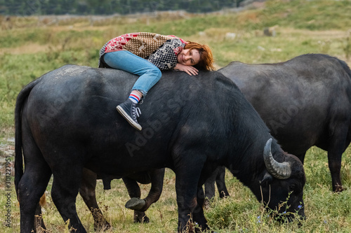Photo  Young woman dressed in a poncho ride on big water buffalo