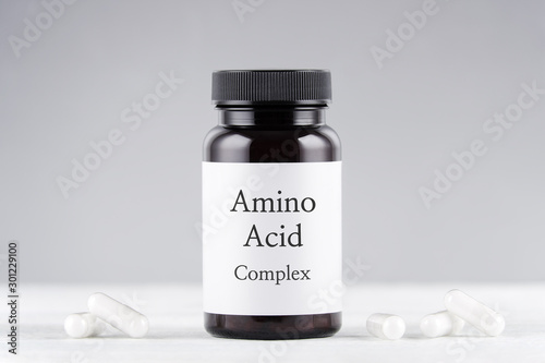 Photo nutritional supplement amino acids bottle and capsules on gray