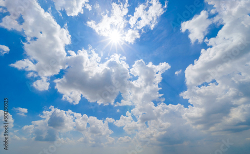 Obraz Clear blue sky with white fluffy clouds in summer season at noon time. Abstract nature background. - fototapety do salonu