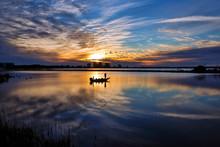 Fisherman In Silhouetter On Lake At Sunset