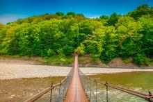 Iron Suspension Bridge. A Suspension Bridge Leads Over A Mountain River