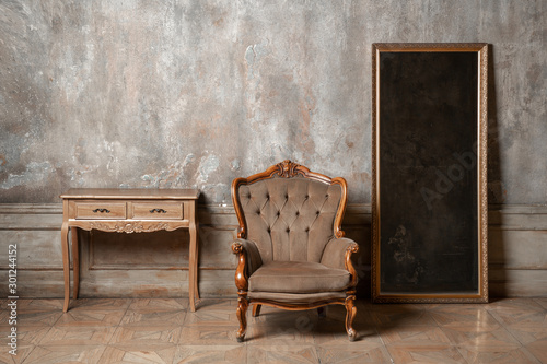 An old chair, a mirror and a table on background of vintage wall Canvas Print