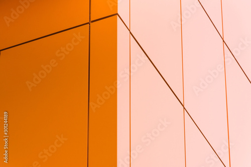 Fotografía  Geometric color elements of the building facade with planes, lines, corners with highlights and reflections for an abstract background and texture of gray, orange, blue colors