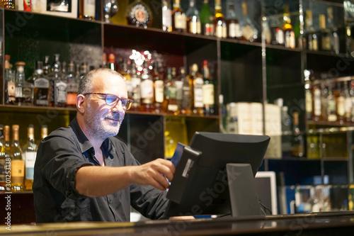 Foto Professional elderly bartender in eyeglases registration of a new order by a cash register
