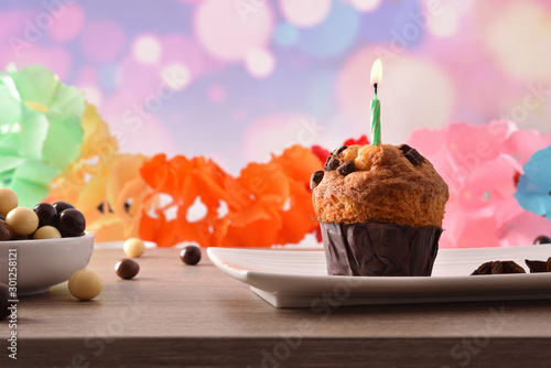 Concept of birthday table with muffin on plate with candle