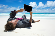 Castaway Businessman Relaxing With Wifi On A Tropical Beach Using His Tablet Computer