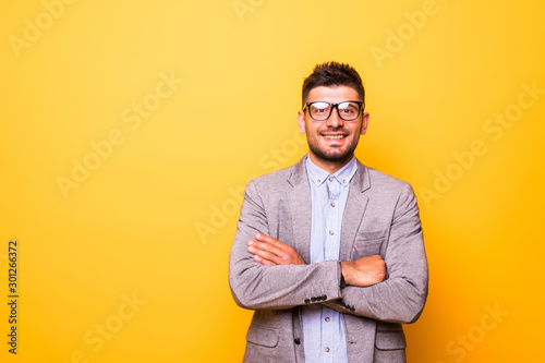 Fototapeta Portrait of a smiling bearded man in glasses standing with arms folded isolated over yellow background obraz