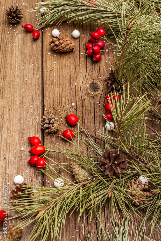 Fototapeta Spirit Christmas background. Fresh dog-rose berries, ball candies, pine branches and cones, artificial snow. Nature decorations, vintage wooden boards