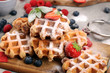 canvas print picture - Traditional belgian waffles with fresh blueberries, sugar and raspberries on rustic table