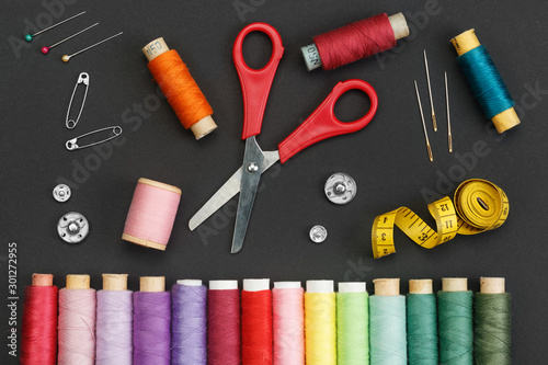 Canvastavla  Colored thread coils, scissors, buttons, needles, pin and a tailor meter on a black background