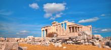 Panoramic Image Of Erechtheion Temple Acropolis, Athens, Greece, With Famous Caryatides In Autumn With Orange Grass And Blue Sky With Clouds