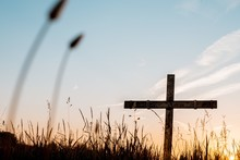 Low Angle Shot Of A Handmade Wooden Cross In A Grassy Field With A Beautiful Sky In The Background